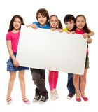 Group of schoolchildren holding white board. Group of school aged teen boys and girls, showing blank placard board to write it on your own text isolated on white Stock Photo