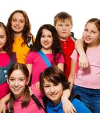 Happy kids from school. Group of school children standing together with backpacks, smiling, laughing, on white Royalty Free Stock Photo