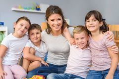 Group of school children with their favorite teacher stock photo