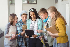 Group of school friends using digital tablet in corridor. At school Stock Photography