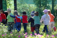 Group of school kids. Group of young little Caucasian school kids lining up to go back to pre-primary school after an outing hiking outdoors in the autumn forest Stock Photos