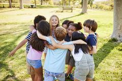 A group of school kids in a huddle outdoors, back view stock image