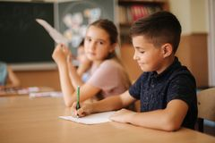Group of school kids with pens and notebooks writing test in classroom. education, elementary school, learning and. People concept royalty free stock image