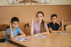 Group of school kids with pens and notebooks writing test in classroom. education, elementary school, learning and. People concept royalty free stock photography