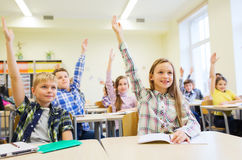 Group of school kids raising hands in classroom Royalty Free Stock Image