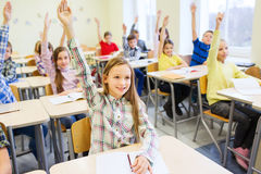 Group of school kids raising hands in classroom Royalty Free Stock Photos