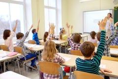 Group of school kids raising hands in classroom stock photo