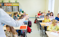 Group of school kids raising hands in classroom Royalty Free Stock Images