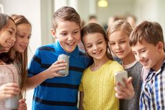 Group of school kids with smartphone and soda cans Royalty Free Stock Image