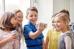 Group of school kids with smartphone and soda cans Stock Photos