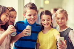 Group of school kids with smartphone and soda cans Royalty Free Stock Images