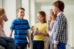 Group of school kids with soda cans in corridor Stock Photos