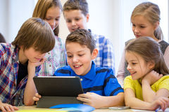 Group of school kids with tablet pc in classroom Royalty Free Stock Photography