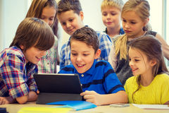 Group of school kids with tablet pc in classroom Royalty Free Stock Photo