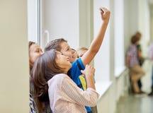 Group of school kids taking selfie with smartphone Stock Image
