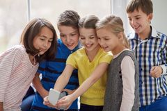 Group of school kids taking selfie with smartphone Stock Photography