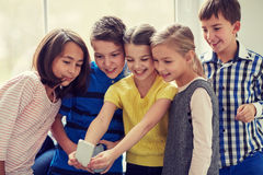Group of school kids taking selfie with smartphone Royalty Free Stock Images