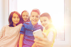 Group of school kids taking selfie with smartphone Royalty Free Stock Image