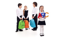 Group of school kids on white background. Group of school kids with colorful bags - isolated Stock Images