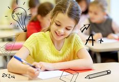 Group of school kids writing test in classroom. Education, elementary school, learning and people concept - group of school kids with notebooks writing test in Royalty Free Stock Images