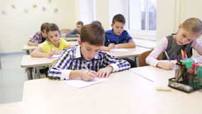 Group of school kids writing test in classroom. Education, elementary school, learning and people concept - group of school kids with pen and papers writing test stock footage