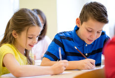Group of school kids writing test in classroom Stock Photo