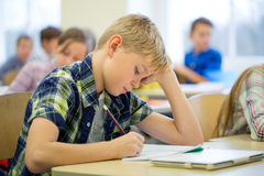 Group of school kids writing test in classroom. Education, elementary school, learning and people concept - group of school kids with pens and notebooks writing Stock Photos
