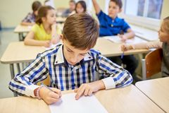 Group of school kids writing test in classroom Royalty Free Stock Photography