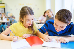 Group of school kids writing test in classroom Stock Photos