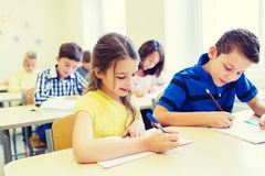 Group of school kids writing test in classroom Royalty Free Stock Image