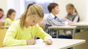 Group of school kids writing test in classroom. Education, elementary school, learning and people concept - group of school kids with pens and papers writing stock video