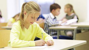 Group of school kids writing test in classroom. Education, elementary school, learning and people concept - group of school kids with pens and papers writing stock video footage