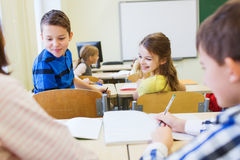 Group of school kids writing test in classroom Stock Photography