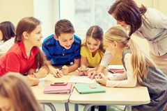 Group of school kids writing test in classroom Stock Image