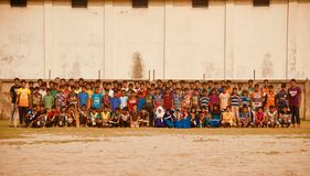 A group of school students sitting in a ground. Isolated editorial photo royalty free stock image