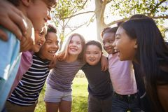 Group of schoolchildren embrace standing in a circle stock images