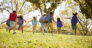Group of schoolchildren running in a field, back view stock photography