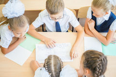 Group of schoolchildren at school classroom sitting at desk Stock Images
