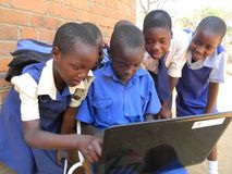 Group of schooldren sharing laptop stock photography