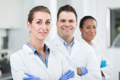 Group of scientists with gloves and gowns in laboratory stock images