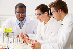 Group Of Scientists Performing Experiment In Laboratory Royalty Free Stock Photos