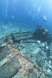 Group of scuba divers exploring a shipwreck. Stock Photography