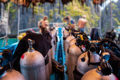 Scuba divers getting ready for diving on a boat full of equipment, Thailand royalty free stock image