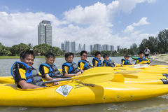 Group of secondary school children learn kayaking at Singapore river. Young teens enjoy while taking kayaking lesson on a sunny day Royalty Free Stock Image