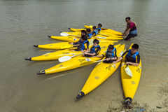 Group of secondary school children learn kayaking at Singapore river. Young teens enjoy while taking kayaking lesson on a sunny day Stock Photography