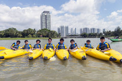 Group of secondary school children learn kayaking at Singapore river. Young teens enjoy while taking kayaking lesson on a sunny day Stock Images