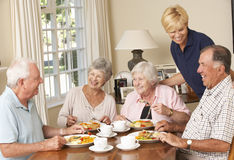 Group Of Senior Couples Enjoying Meal Together In Care Home With Stock Photo