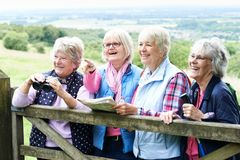 Group Of Senior Female Friends Hiking In Countryside. Senior Female Friends Hiking In Countryside Stock Photos