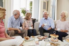 Group Of Senior Friends Enjoying Afternoon Tea At Home Together royalty free stock photos