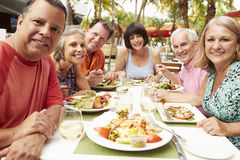 Group Of Senior Friends Enjoying Meal In Outdoor Restaurant Royalty Free Stock Images
